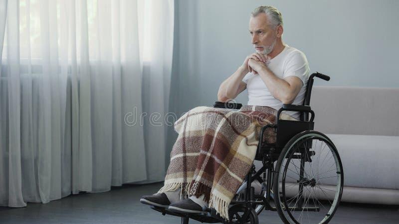 坐在轮椅的老不适的男性和祈祷,消沉和可怕的疾病 免版税库存照片