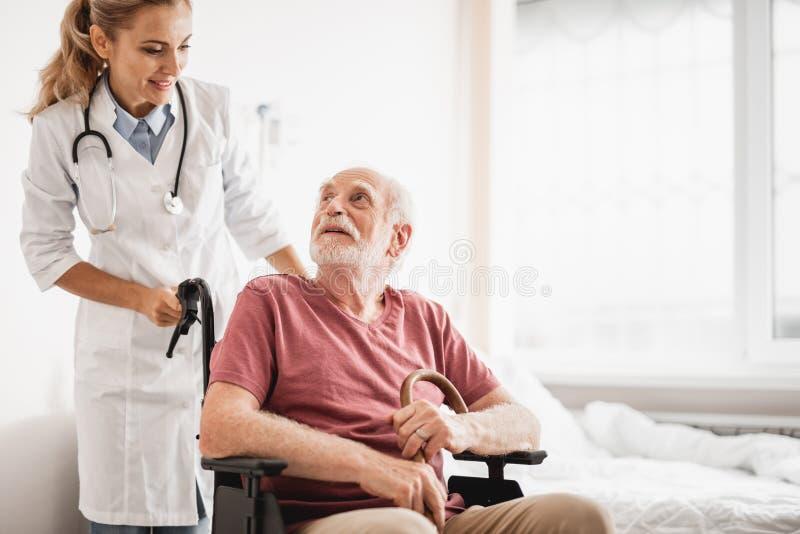 坐在轮椅的老人,当站立的医生后边时 库存照片