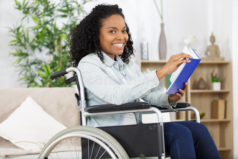 坐在轮椅看书的年轻女人 库存照片