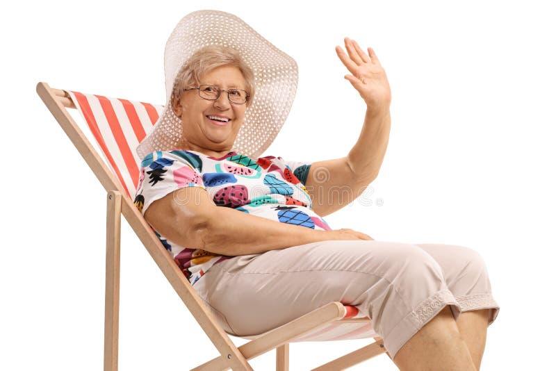 坐在轻便折叠躺椅和挥动的愉快的资深妇女 免版税库存照片