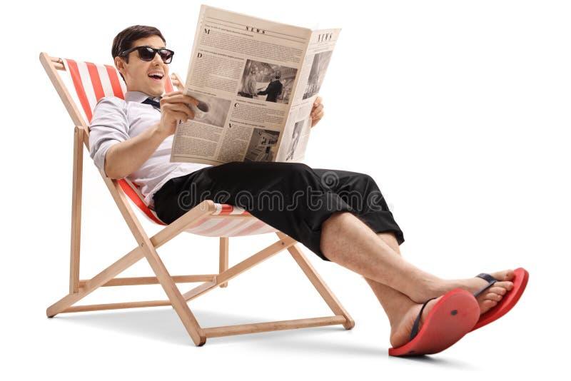 坐在轻便折叠躺椅和读报纸的商人 库存图片