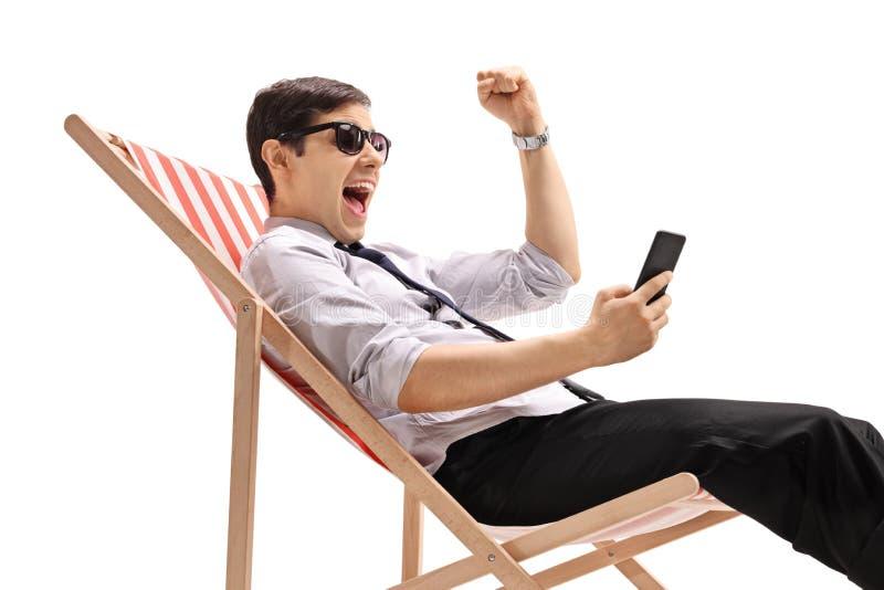 坐在轻便折叠躺椅的年轻商人看电话和打手势幸福 免版税图库摄影