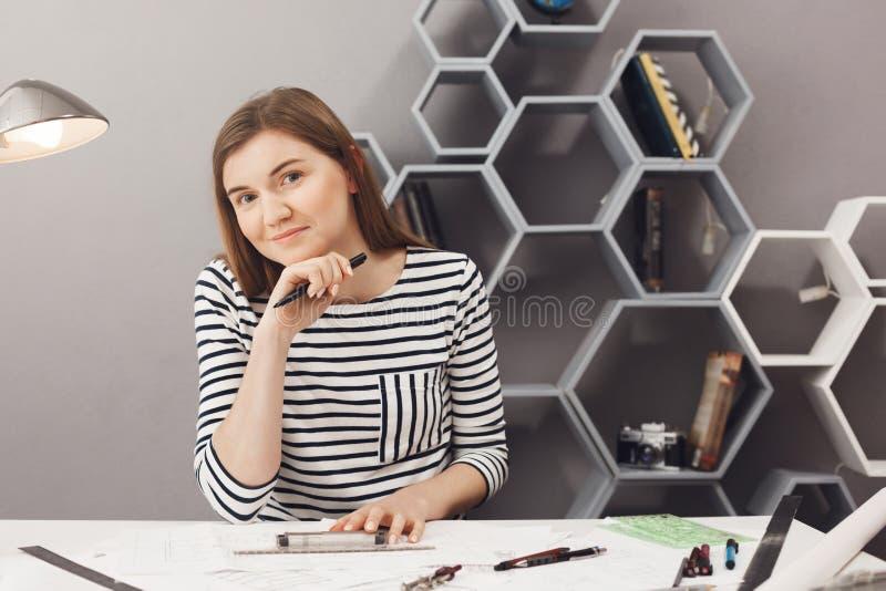 坐在轻松的共同工作的空间的桌上的年轻快乐的深色头发的女性自由职业者的设计师画象,完成工作 免版税图库摄影