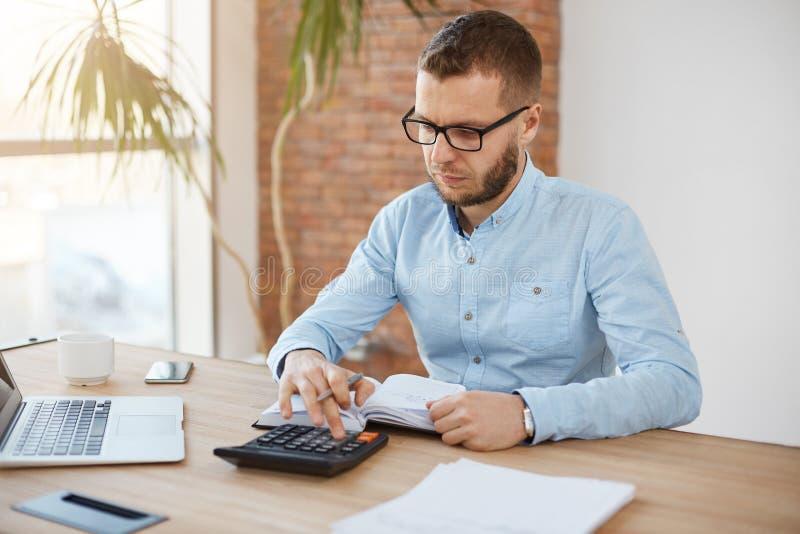 坐在轻的舒适的公司办公室的玻璃和蓝色衬衣的成人严肃的有胡子的白种人财务经理 免版税库存照片