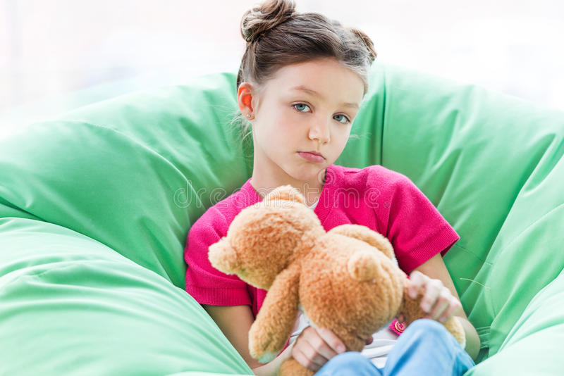 坐在辎重袋椅子和拿着玩具熊的严肃的小女孩 库存图片