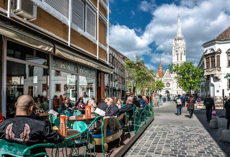 坐在边路咖啡馆的游人 免版税库存图片