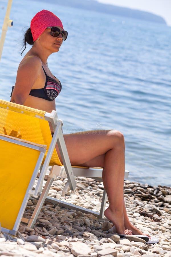 坐在遮阳伞下的被晒黑的白种人妇女在Pebble海滩在蓝色海水、穿戴的泳装和红色方巾附近 免版税图库摄影