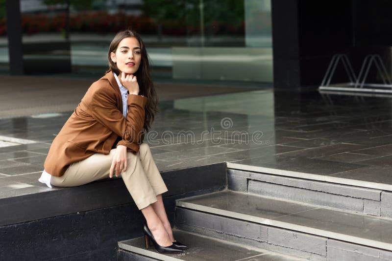坐在都市的办公楼外面的年轻女实业家 免版税图库摄影