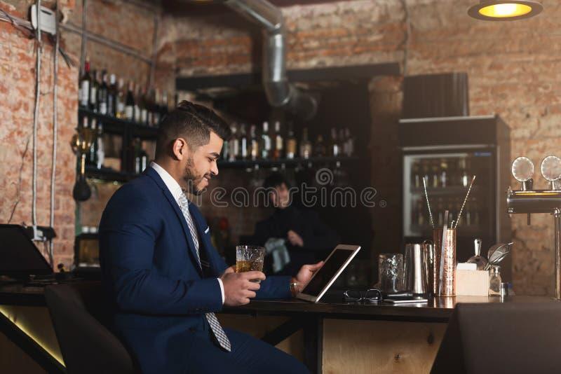 坐在酒吧柜台和使用数字式片剂的年轻人 免版税库存图片