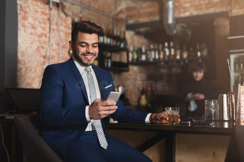 坐在酒吧柜台和使用智能手机的年轻人 免版税库存图片
