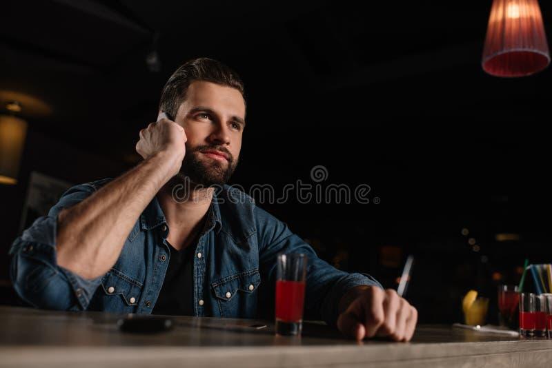 坐在酒吧柜台和谈话的访客 库存照片