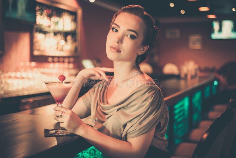 坐在酒吧柜台附近的妇女 图库摄影