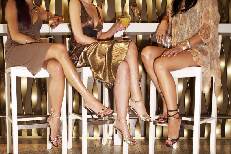 坐在酒吧的时髦地加工好的妇女 免版税库存照片