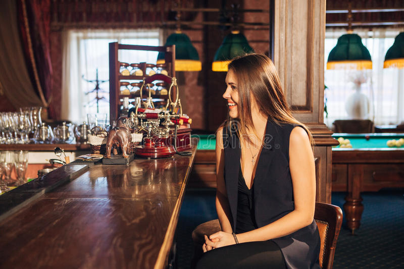 坐在酒吧的美丽的少妇谈话与侍酒者 免版税库存图片