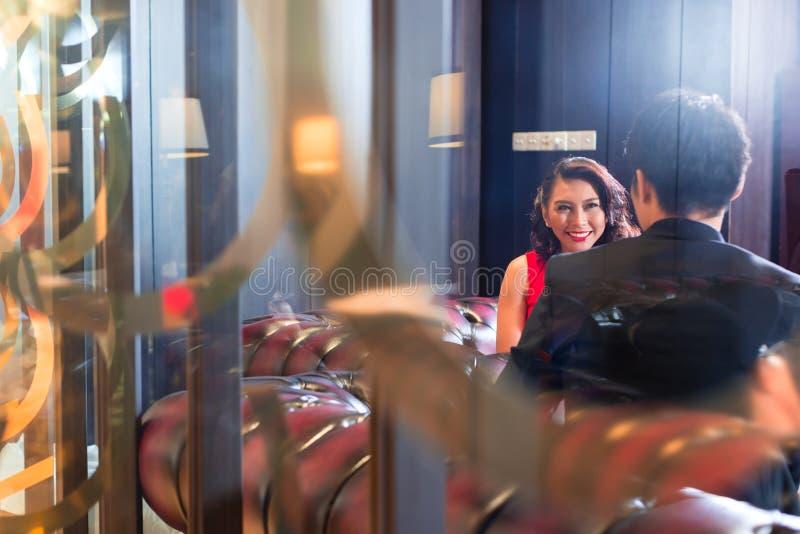 坐在酒吧聊天的亚洲夫妇 免版税图库摄影