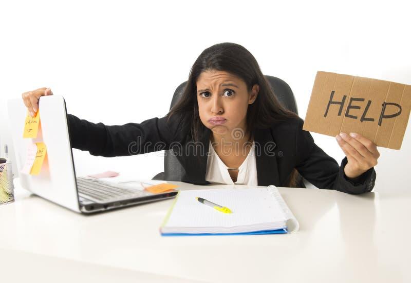 坐在重音的办公桌的年轻繁忙的绝望拉丁女实业家藏品帮助标志担心 免版税库存照片