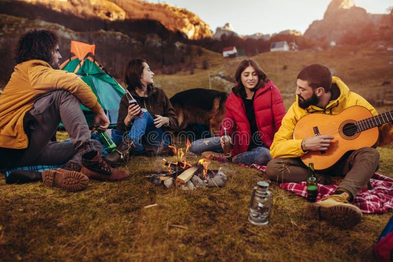 坐在野营的篝火附近的微笑的朋友 库存照片