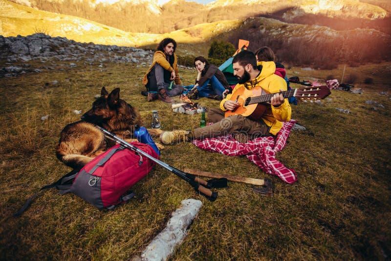 坐在野营的篝火附近的微笑的朋友 图库摄影