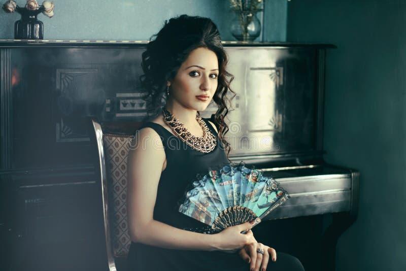 坐在钢琴旁边的华美的女孩 免版税库存图片