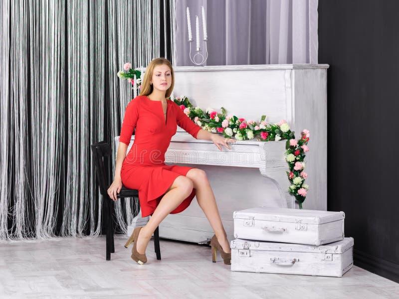 坐在钢琴的女孩 免版税图库摄影