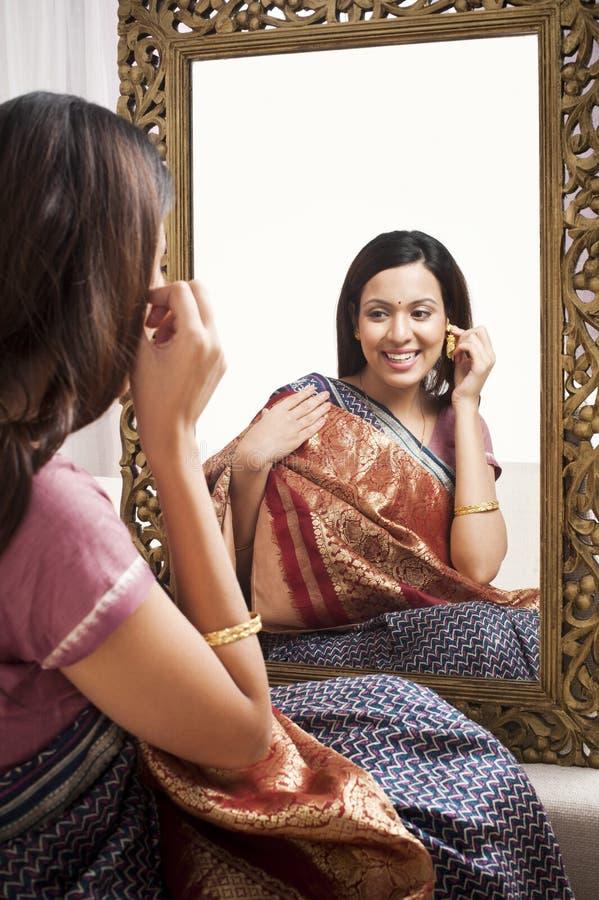 坐在镜子前面的妇女 免版税图库摄影