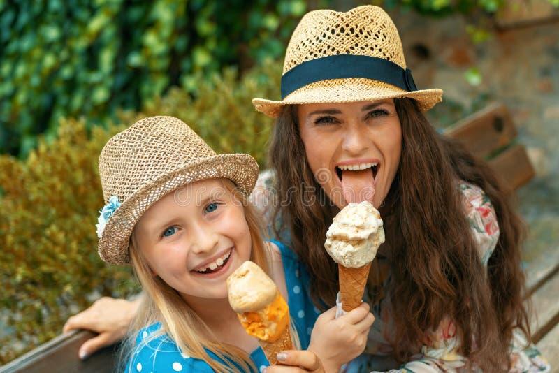 坐在长凳和吃冰淇淋的母亲和女儿 免版税库存图片
