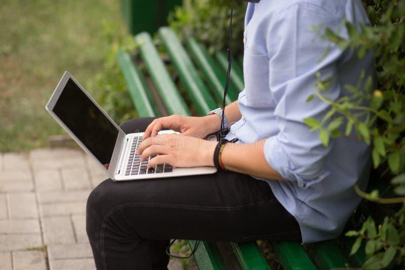 坐在长凳的年轻人的播种的图象在公园,使用膝上型计算机 免版税库存图片