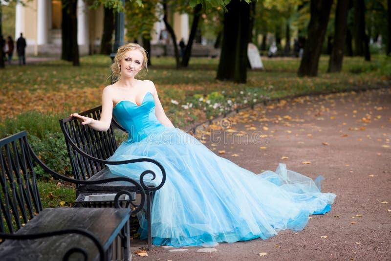 坐在长凳的长的蓝色礼服的可爱的妇女在公园 免版税库存照片