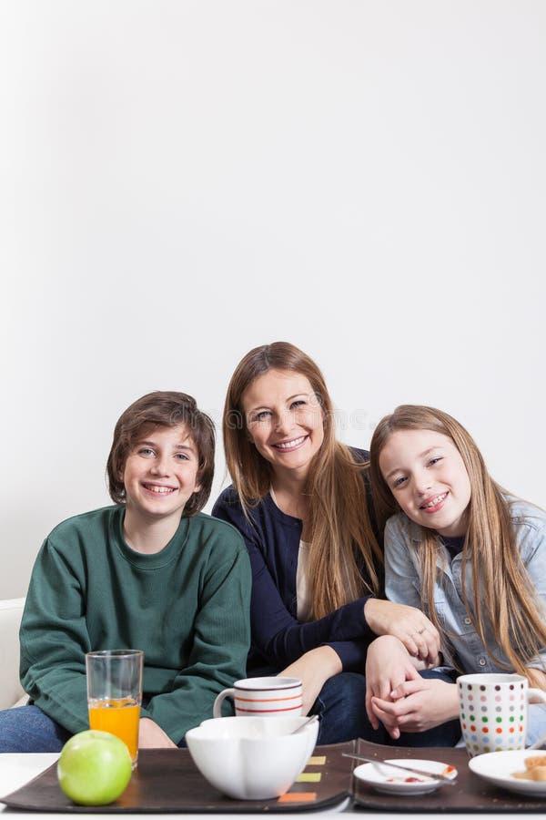 坐在长沙发的愉快的家庭 免版税库存照片