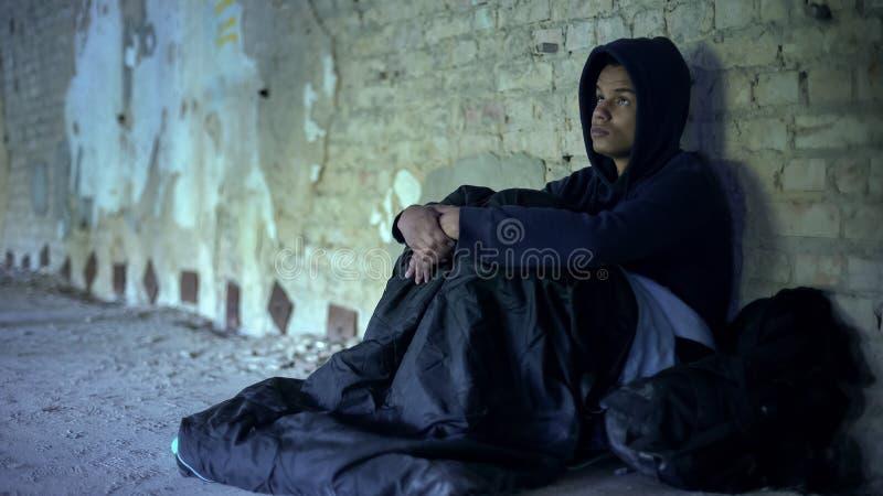 坐在门户的无家可归的难民,准备对隔夜在睡袋 库存图片