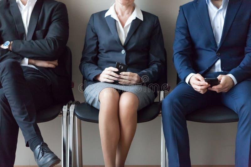 坐在队列等待的工作面试的椅子的商人 免版税库存图片