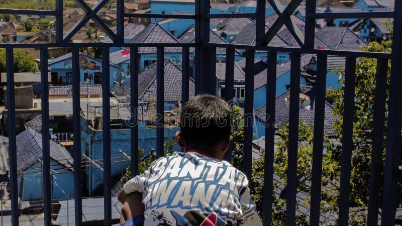坐在阳台附近的男孩有蓝色村庄视图 库存照片