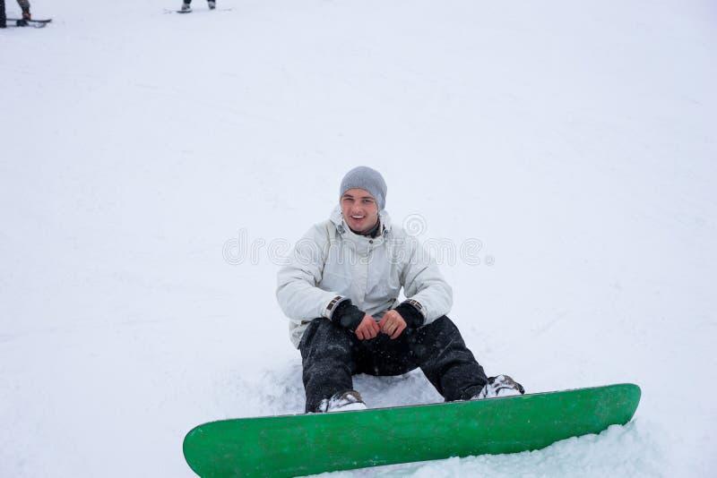 坐在雪的年轻人雪板运动 免版税库存图片