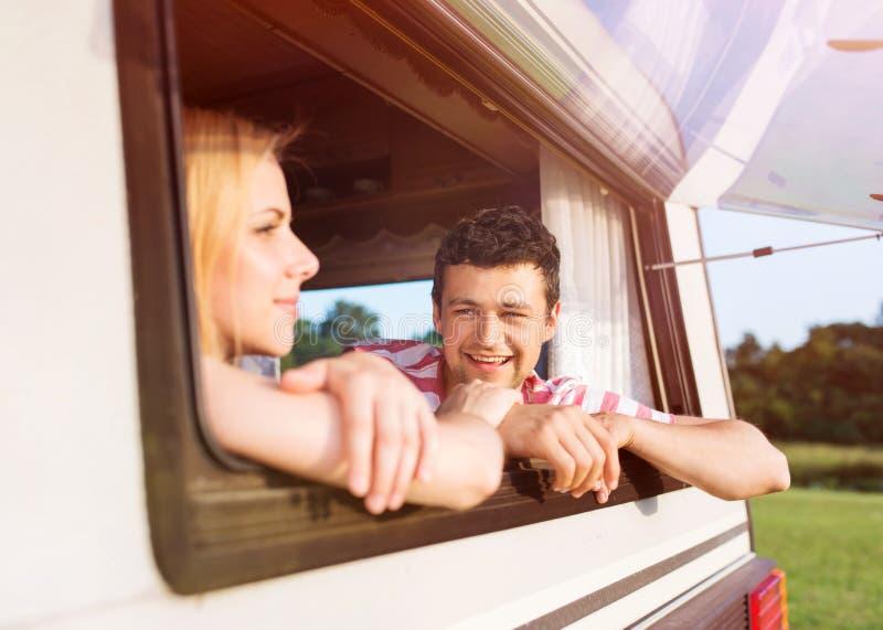 坐在露营者货车的年轻夫妇 图库摄影