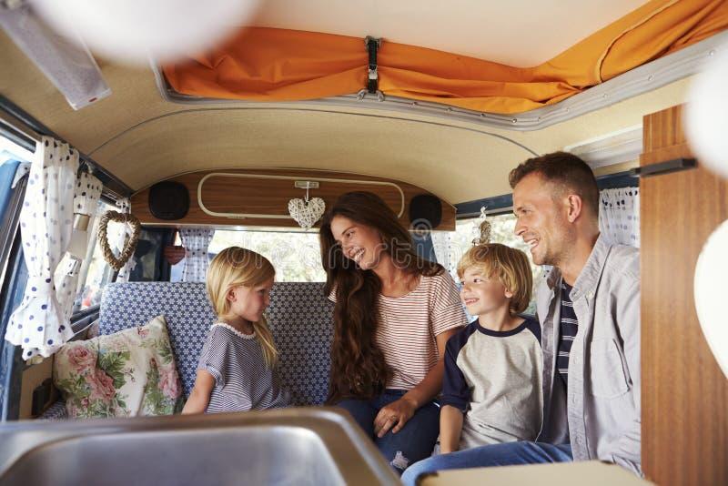 坐在露营者货车里面的家庭看彼此 免版税库存图片
