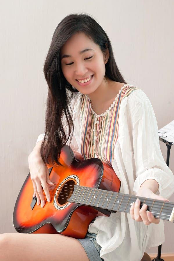 坐在音乐屋子和弹的微笑的亚裔美女吉他 库存照片