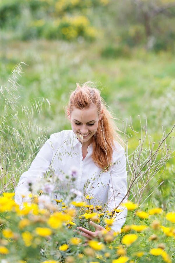 坐在领域的花中的微笑的红头发人妇女 图库摄影