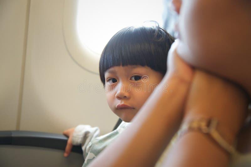 坐在飞机的靠窗座位的小男孩:看camer 免版税库存照片