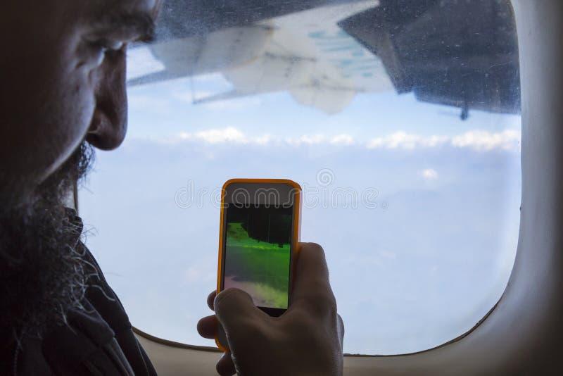 坐在飞机窗口和拍照片的有胡子的人在电话 库存照片