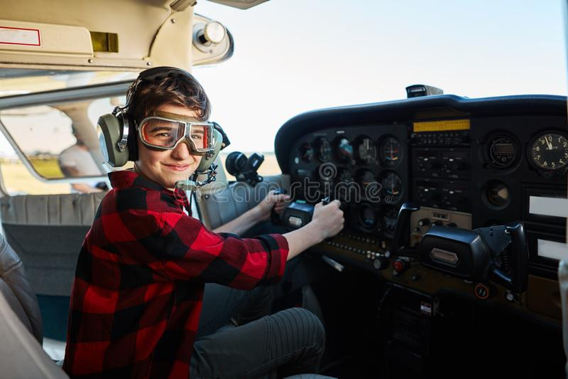坐在飞机驾驶舱内的飞行员玻璃和耳机的逗人喜爱的男孩 免版税库存图片