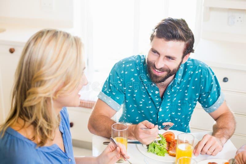 坐在餐桌谈话的年轻夫妇 免版税库存照片