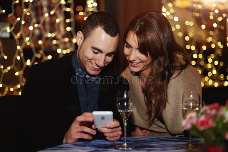 坐在餐馆和人的美好的年轻夫妇显露他喜爱的照片 免版税图库摄影