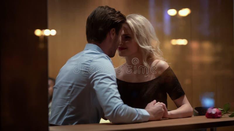 坐在餐馆和挥动与帅哥,关系的白肤金发的妇女 免版税库存照片