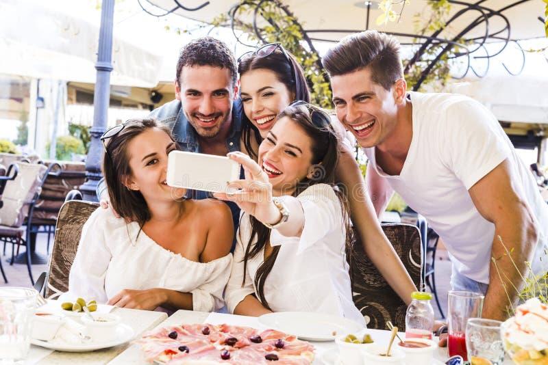 坐在餐馆和taki的小组年轻美丽的人民 库存图片