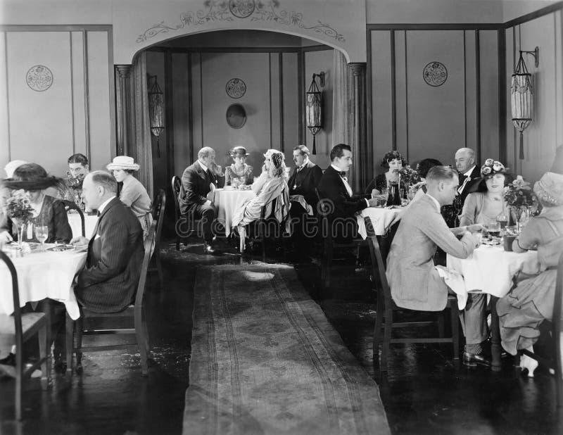 坐在餐馆的人吃晚餐(所有人被描述不更长生存,并且庄园不存在 供应商 免版税库存照片