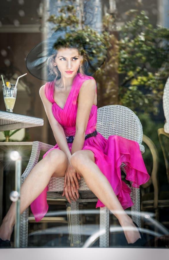 坐在餐馆的桃红色礼服的时兴的可爱的少妇,在窗口之外 美好女性摆在餐馆 库存图片