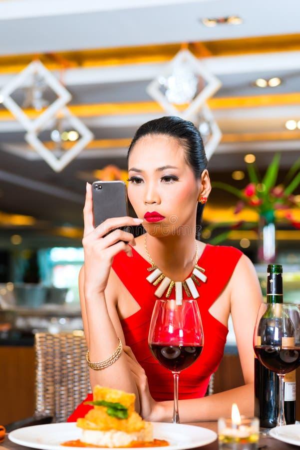 坐在餐馆的年轻亚裔妇女 图库摄影