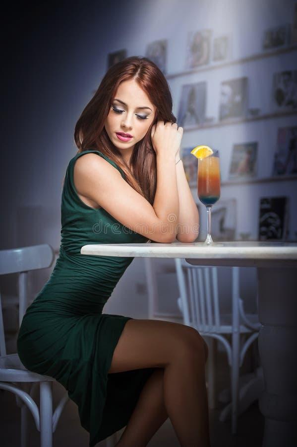 坐在餐馆的绿色礼服的时兴的可爱的少妇 摆在与饮料的典雅的风景的美丽的红头发人 图库摄影