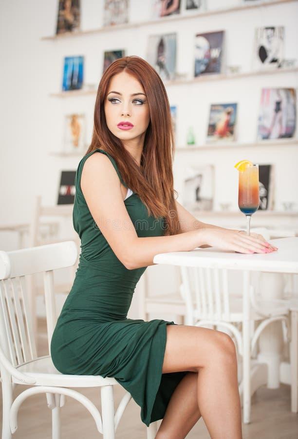 坐在餐馆的绿色礼服的时兴的可爱的少妇 摆在典雅的风景的美丽的红头发人用汁液 库存图片