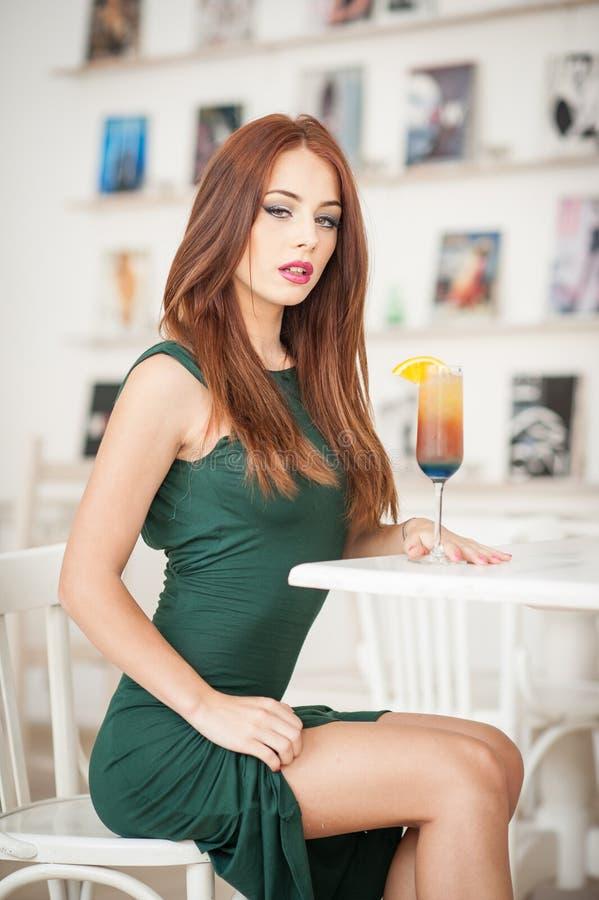坐在餐馆的绿色礼服的时兴的可爱的少妇 摆在典雅的风景的美丽的红头发人用汁液 免版税库存照片